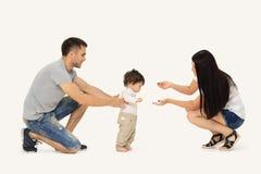 Retrato de uma família feliz que ensine uma criança andar imagens de stock royalty free