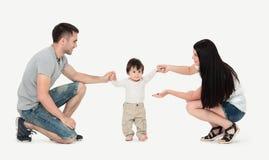 Retrato de uma família feliz que ensine uma criança andar imagem de stock royalty free