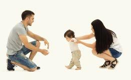 Retrato de uma família feliz que ensine uma criança andar fotos de stock