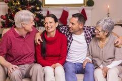 Retrato de uma família feliz que senta-se e que fala no sofá Imagens de Stock Royalty Free