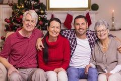 Retrato de uma família feliz que senta-se no sofá Imagem de Stock Royalty Free