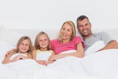 Retrato de uma família que encontra-se na cama imagens de stock royalty free