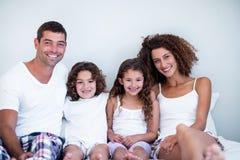Retrato de uma família que senta-se junto na cama fotos de stock royalty free