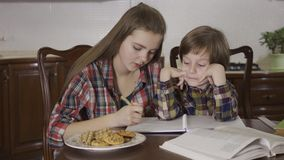 Retrato de uma irmã mais idosa e de um irmão mais novo que aprendem lições Uma menina faz trabalhos de casa com um rapaz pequeno vídeos de arquivo