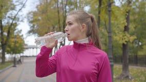 Retrato de uma jovem caucasiana em jato de esporto cor-de-rosa se aproximando da câmera, bebendo água e correndo para a frente filme