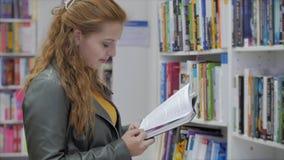 Retrato de uma jovem linda com cabelo vermelho brilhante em óculos, linda menina lendo na universidade de biblioteca de livros vídeos de arquivo