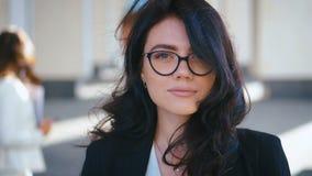 Retrato de uma jovem linda empresária nos óculos perto do prédio de escritórios moderno Garota olhando a câmera e sorrindo filme