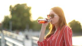 Retrato de uma jovem mulher atrativa que olha a c?mera A menina de sorriso está bebendo a cerveja Menina de riso com caucasiano filme