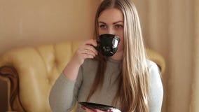 Retrato de uma jovem mulher atrativa que senta-se no sofá na casa familiar da sala de visitas, café fresco bebendo filme