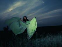 Retrato de uma jovem mulher bonita no fundo do por do sol Imagem de Stock