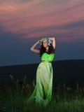 Retrato de uma jovem mulher bonita no fundo do por do sol Fotografia de Stock Royalty Free