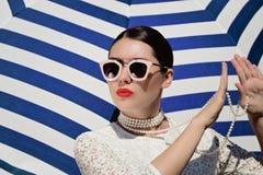 Retrato de uma jovem mulher bonita no vestido branco do la?o, colar da p?rola e claro brancos - ?culos de sol cor-de-rosa fotografia de stock
