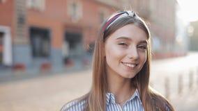 Retrato de uma jovem mulher bonita que olha na câmera e na posição de sorriso no fundo velho da rua Menina video estoque