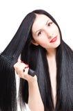 Retrato de uma jovem mulher bonita que penteia seu cabelo preparado longo Fotografia de Stock Royalty Free