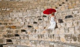 Retrato de uma jovem mulher bonita que senta-se sob um guarda-chuva vermelho Imagens de Stock