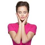 Retrato de uma jovem mulher com emoções e mãos calmas na cara Fotografia de Stock