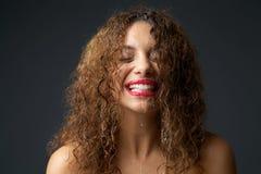 Retrato de uma jovem mulher com o gotejamento da água da cara Foto de Stock