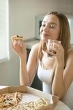 Retrato de uma jovem mulher com pizza em sua mão fotos de stock