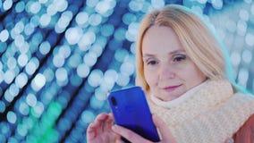 Retrato de uma jovem mulher com um smartphone no fundo de festões obscuras da rua do bokeh imagens de stock royalty free