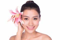 Retrato de uma jovem mulher com uma flor do lírio no branco Foto de Stock