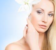 Retrato de uma jovem mulher com uma flor do lírio no azul Fotografia de Stock Royalty Free