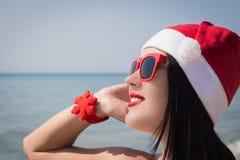Retrato de uma jovem mulher de sorriso feliz no chapéu de Santa Claus Fotografia de Stock Royalty Free