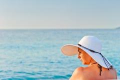 Retrato de uma jovem mulher em um chapéu branco em um fundo do mar imagem de stock royalty free
