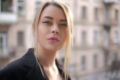 Retrato de uma jovem mulher em um close-up preto do terno contra um fundo de uma cidade obscura nos raios do sol de ajuste Fotografia de Stock Royalty Free