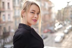 Retrato de uma jovem mulher em um close-up preto do terno contra um fundo de uma cidade obscura nos raios do sol de ajuste Imagens de Stock
