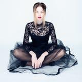 Retrato de uma jovem mulher em um vestido preto do laço Imagens de Stock
