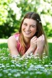 Retrato de uma jovem mulher feliz que encontra-se fora na grama e nas flores Imagem de Stock