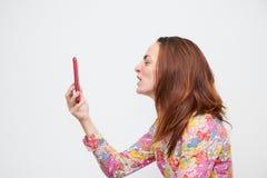 Retrato de uma jovem mulher na camisa da cor que grita em um telefone celular isolado em um fundo branco a cor do cabelo é marrom foto de stock
