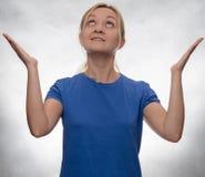 Retrato de uma jovem mulher na camisa ocasional azul que aponta acima fotos de stock royalty free