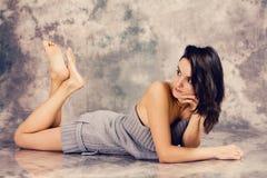 Retrato de uma jovem mulher no estúdio, encontrando-se no assoalho Fotos de Stock