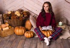 Retrato de uma jovem mulher no interior da casa do outono com um livro Menina pensativa com livro Abóbora e conceito do outono Imagens de Stock Royalty Free