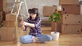 Retrato de uma jovem mulher nos vidros da realidade virtual que sentam-se no assoalho ao lado das caixas