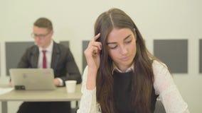 Retrato de uma jovem mulher pensativa no vestuário formal que senta-se no primeiro plano no escritório quando seu colega masculin vídeos de arquivo