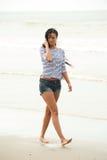 Retrato de uma jovem mulher que anda na praia apenas imagens de stock