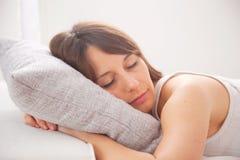 Retrato de uma jovem mulher que dorme na cama Fotos de Stock Royalty Free