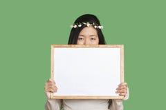 Retrato de uma jovem mulher que esconde sua cara com um whiteboard vazio sobre o fundo verde Fotos de Stock
