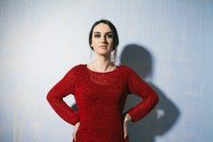 Retrato de uma jovem mulher que está no fundo azul com cintura das mãos Fotografia de Stock Royalty Free