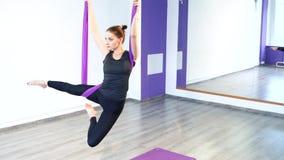 Retrato de uma jovem mulher que faz a ioga antigravitante O conceito da harmonia e da tranquilidade filme