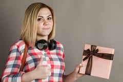 Retrato de uma jovem mulher que guarda um presente Estudante em s quadriculado foto de stock