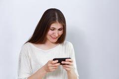 Retrato de uma jovem mulher que joga um jogo ou que olha um filme no smartphone Foto de Stock Royalty Free