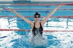 Retrato de uma jovem mulher que salta na piscina Fotos de Stock