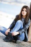 Retrato de uma jovem mulher que senta-se no passeio Imagens de Stock Royalty Free