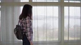 Retrato de uma jovem mulher que usa um telefone ao estar por uma grande janela video estoque