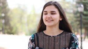 Retrato de uma jovem mulher que veste o vestido ocasional, fora Retrato de uma menina com penteado longo no fundo urbano video estoque
