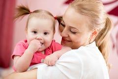 Retrato de uma mãe alegre e de sua filha do bebê Fotos de Stock Royalty Free