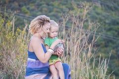 Retrato de uma mãe bonita nova com seu filho pequeno que está descansando no país imagens de stock